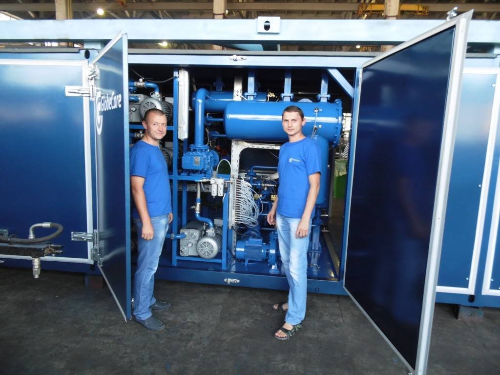 GlobeCore employees in front of oil regeneration equipment